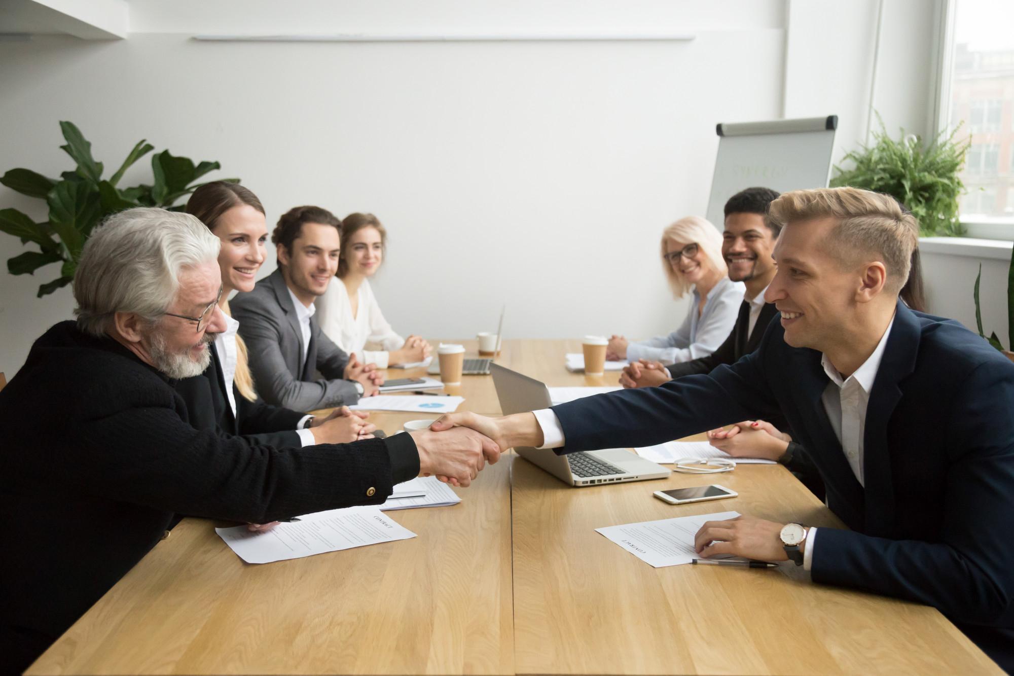 senior-investor-buying-startup-handshaking-young-entrepreneur-group-meeting